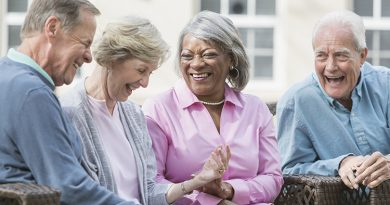 Multiracial senior friends sitting outdoors on patio talking