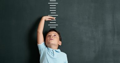 Child measuring his height on wall. He is growing up so fast.