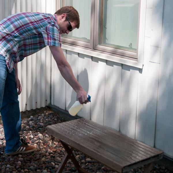 spraying teak cleaner solution