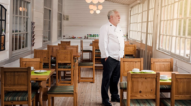 Restaurant-owner-standing-in-his-empty-restaurant