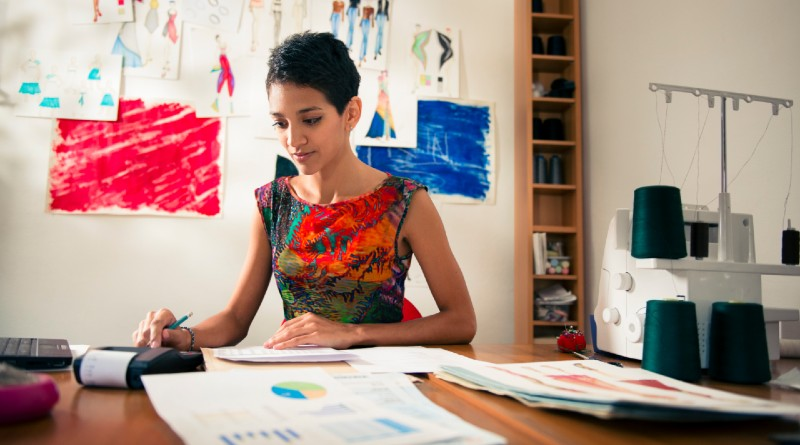 money-and-financial-planning-young-hispanic-self-employed-woman-checking-bills-and-doing-budget-with-calculator-in-fashion-design-studio