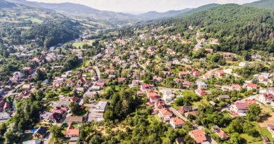 test-drive-a-neighborhood-with-aerial-view-of-small-town-with-many-hills-and-forest-surrounding-it