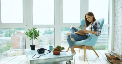 young-attractive-woman-reads-book-and-drink-coffee-sitting-on-balcony-in-new-modern-loft-apartment